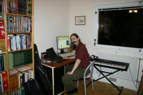 Bild: På plats.     Här sitter jag omgiven av datorer, musikinstrument och     serier.