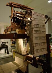 Bild: Jacquardvävstol.  Mönstret den skulle väva fanns lagrat på       hålkorten så den automatiskt kunde lyfta rätt trådar.