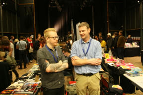 Bild: Daniel Thollin och förläggaren Jonas Andersson, med en     del av mässvimlet i bakgrunden.
